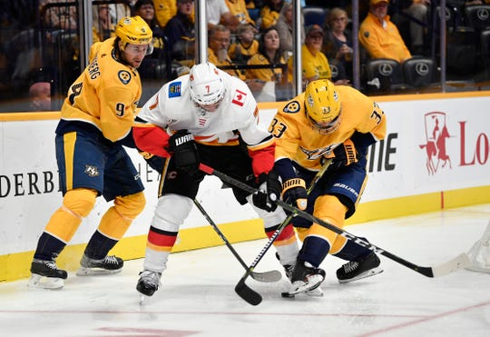 Calgary Flames defenseman TJ Brodie (7) and Nashville Predators left wing Viktor Arvidsson (33) battle for the puck in the third period of the home opener at Bridgestone Arena in Nashville, Tenn., Tuesday, Oct. 9, 2018.