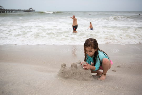 Adela Suzaya, 4, on vacation with her family from Argentina, tries to salvage her sand castle as it gets hit by waves pushed ashore by Hurricane Michael on Wednesday, Oct. 10, 2018, at the Naples Pier.