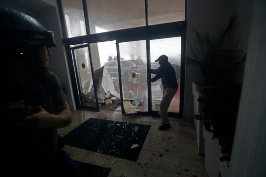A hotel employee holds a glass door closed as it breaks from flying debris during Hurricane Michael in Panama City Beach, Fla., Wednesday, Oct. 10, 2018.