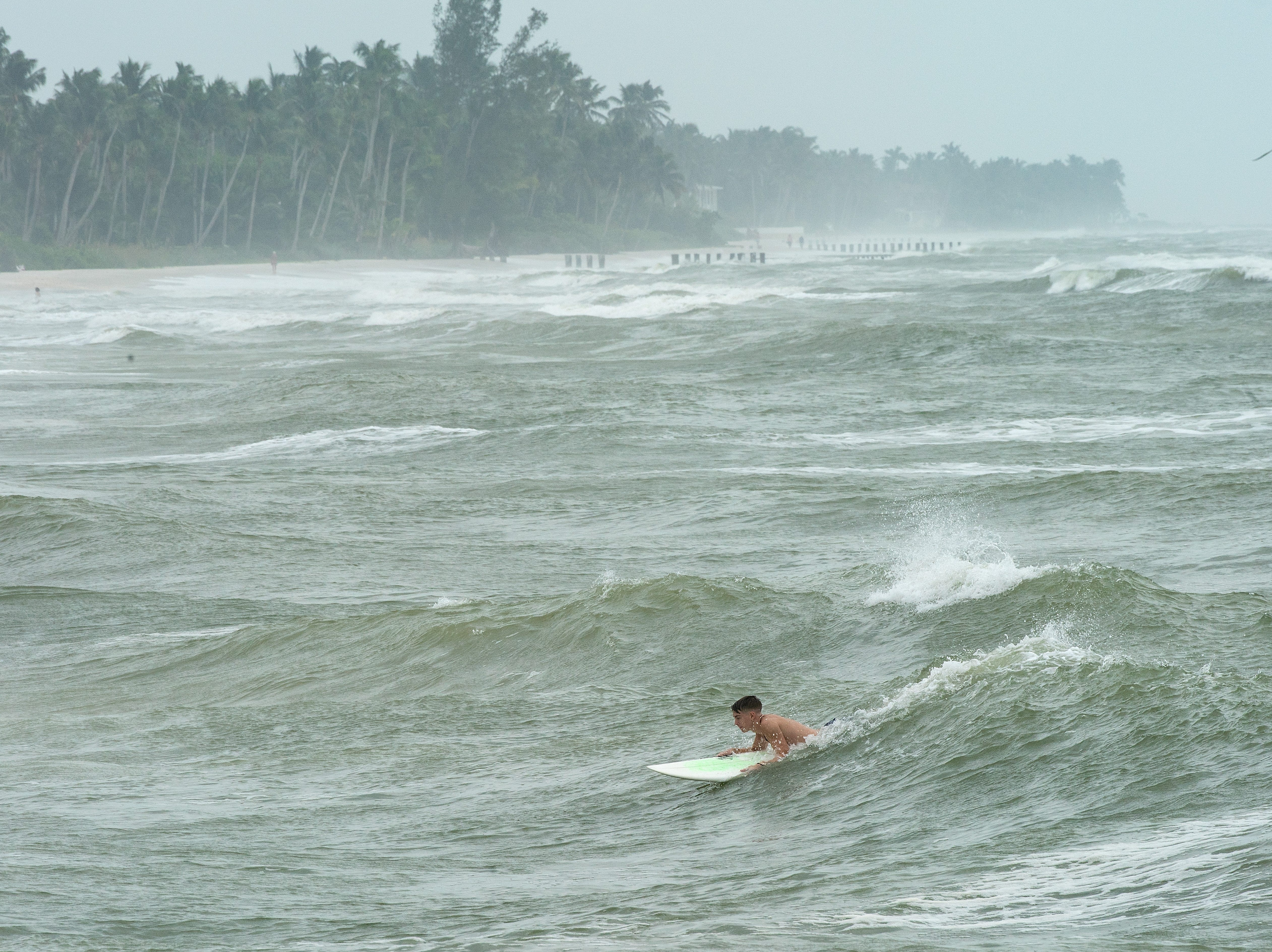A surfer braving strong winds attempts to ride a large wave as Hurricane Michael, even from hundreds of miles away, continues to push water ashore near the Naples Pier on Wednesday, Oct. 10, 2018.