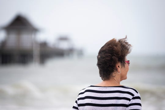 The wind blows through Carol Trask's hair as she watches waves crash by the Naples Pier on Wednesday, Oct. 10, 2018.