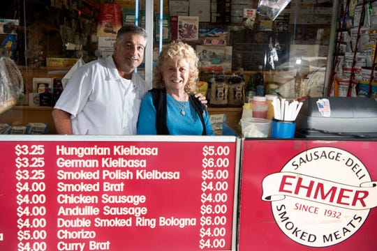 Dolores Santucci 92, poses for a pictures with her son, Michael Santucci, owner of Karl Ehmer Quality Meats in Hillsdale. Dolores sells a wide variety of grilled hot dogs, sausages, bratwurst and kielbasa from a cart in front of her son's store on Broadway in downtown Hillsdale.
