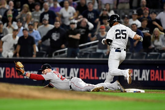 Boston Red Sox's Steve Pearce, left, slides for the ball tagging out New York Yankees' Gleyber Torres (25) for the final out of Game 4, with the Red Sox winning American League Division Series, 4-3, on Tuesday, Oct. 9, 2018, in New York.
