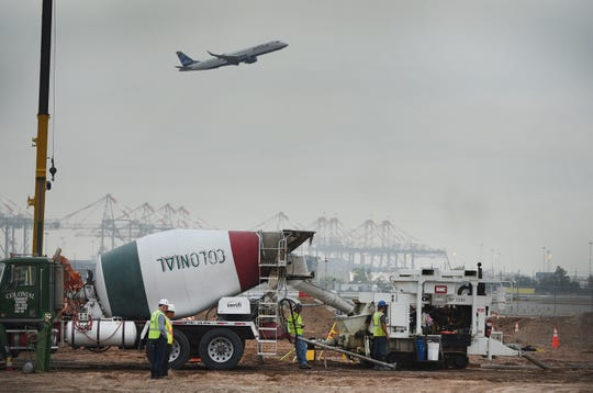 An air plane flying as workers are seen at the site of new Terminal One in Newark Liberty International Airport on 10/10/18.