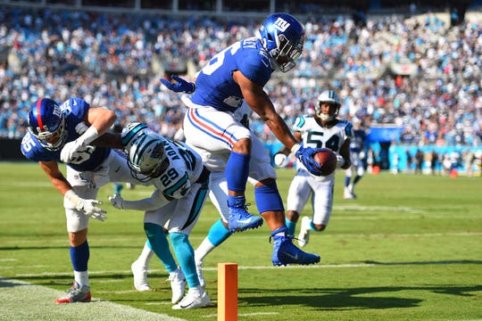 Oct 7, 2018; Charlotte, NC, USA; New York Giants running back Saquon Barkley (26) scores a touchdown as Carolina Panthers free safety Mike Adams (29) defends in the fourth quarter at Bank of America Stadium.