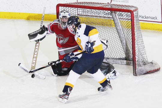 Parsippany goalie Ryan Daoud swipes the puck away from Pequannock's Shawn Lacorta during Haas Cup competition at Mennen Arena Feb. 13, 2012.