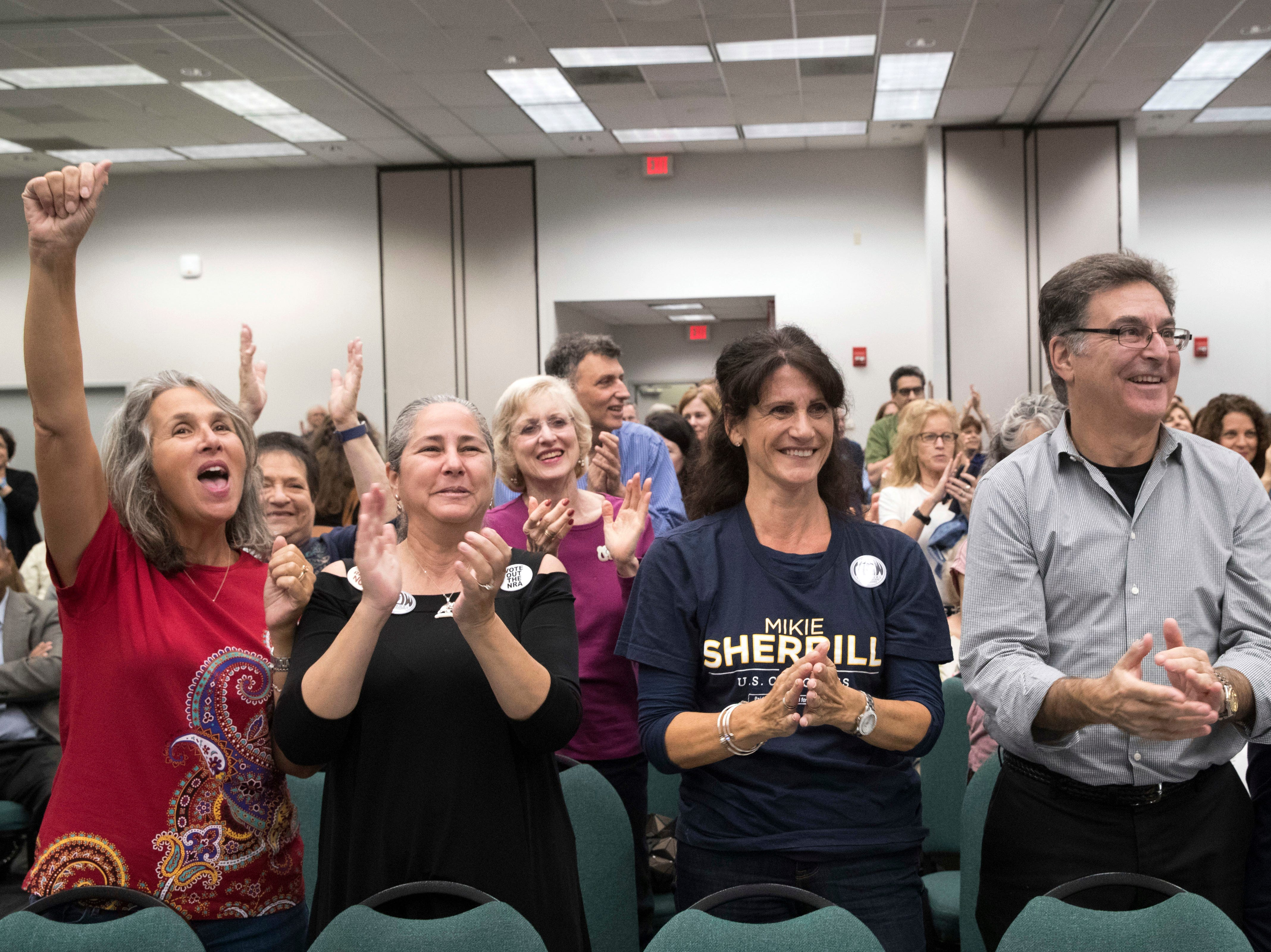 Supporters of Democratic congressional candidate Mikie Sherrill cheer as she arrives for a candidate forum at the UJC of MetroWest New Jersey, Tuesday, Oct. 9, 2018, in Whippany, N.J. (AP Photo/Mary Altaffer)
