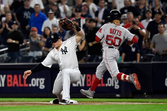 New York Yankees first baseman Luke Voit gets Boston Red Sox's Mookie Betts (50) out at first in the first inning in Game 4 of the American League Division Series on Tuesday, Oct. 9, 2018, in New York.