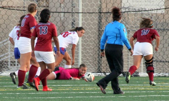 Sophomore Lady 'Cat goal keeper Palmira Valentine lays out in front of the Deming goal to turn away a Las Cruces High scoring attempt.