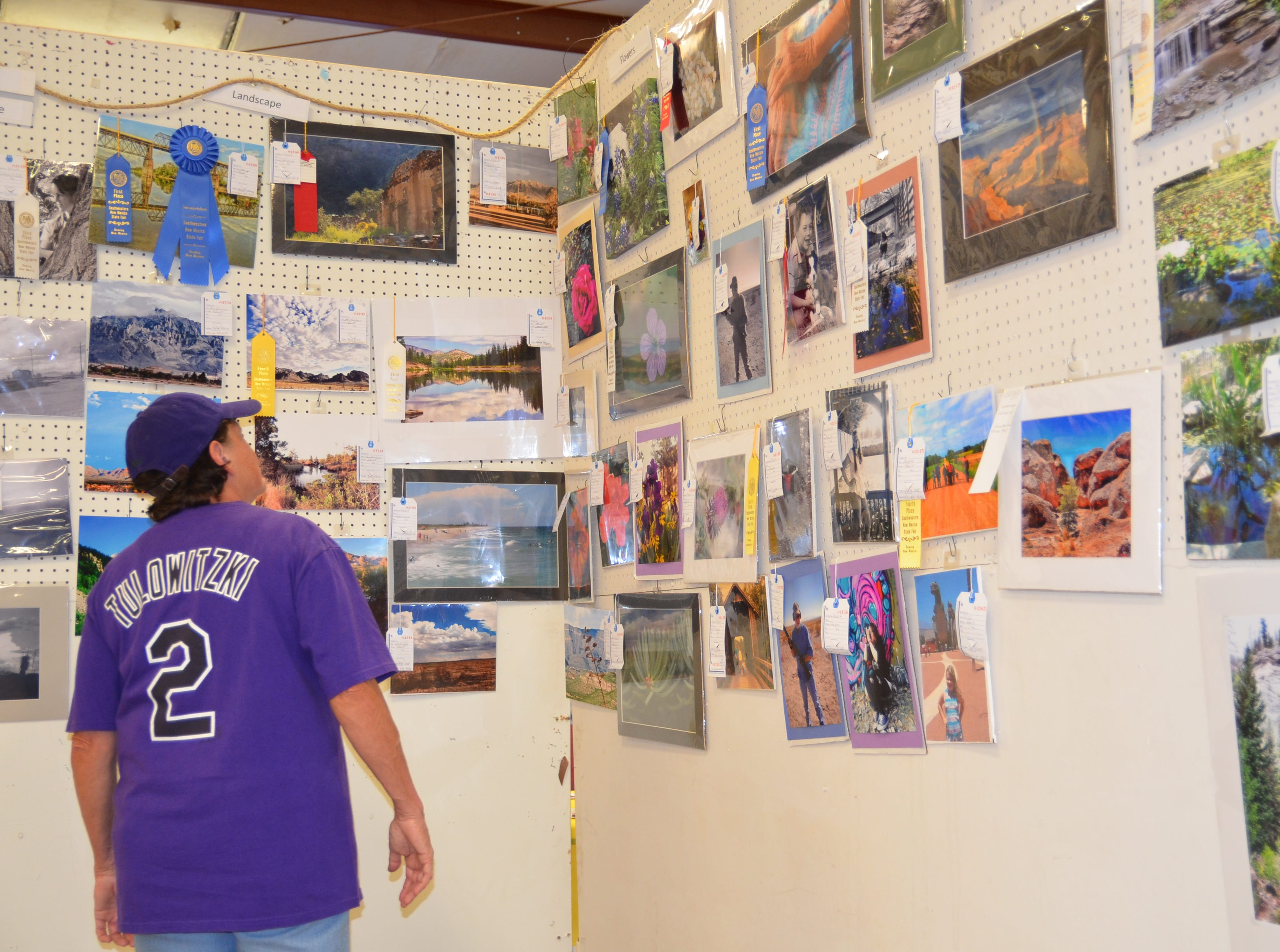 A fair-goer gazes over the prized photo entries at the Photography Show during the Agtoberfest at the Southwestern New Mexico State Fair on Friday.