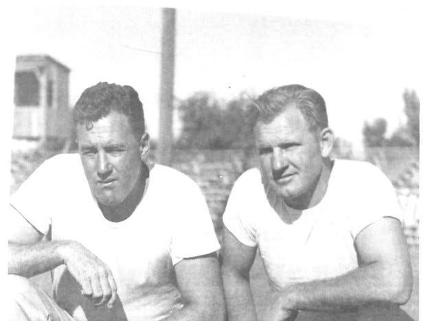 Cavemen Football Coaches Ralph Bowyer (43) and Lionel Jordan (25) squatting together at the field circa	1957.