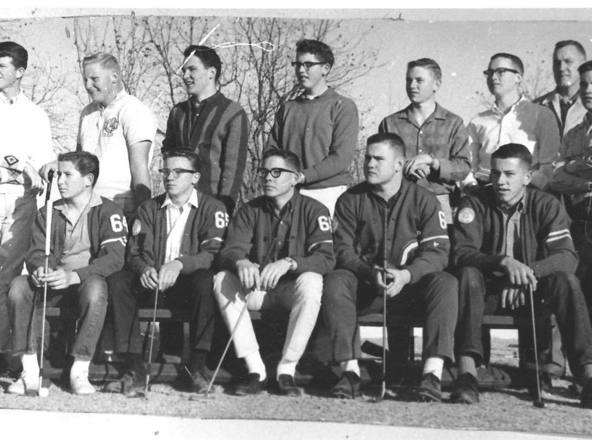 The 1963/1964 Cavemen Golf Team of 12, all unknown, plus Coach Ralph Bowyer, back right.