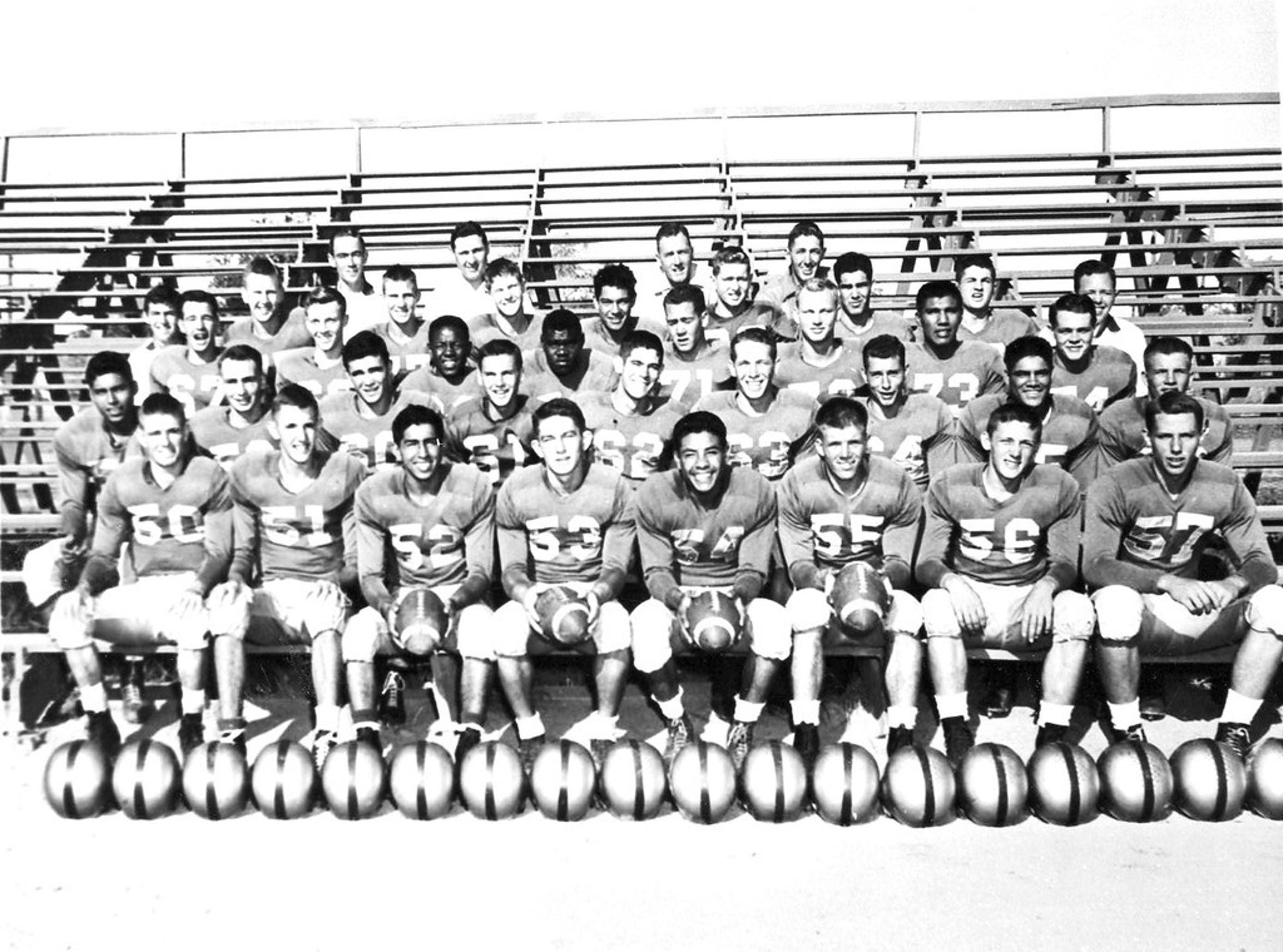 Circa 1953, the Cavemen Football team posed in the bleachers. Pictured in back are Coach Smith, Coach Reid McCloskey, Head Coach Ralph Bowyer.