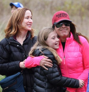 St. Regis' late track and cross country coach Deanna Wile (far right) hugs runner Audrey DaDamio, now a sophomore at Seaholm, with Audrey's mother Lynn enjoying the interaction. Wile died late last month after a battle with breast cancer.