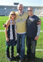 Greg Marx (center) stands on the field at Notre Dame stadium with daughter Mckenzie Nuedling (left) and son-in-law Sean Nuedling.