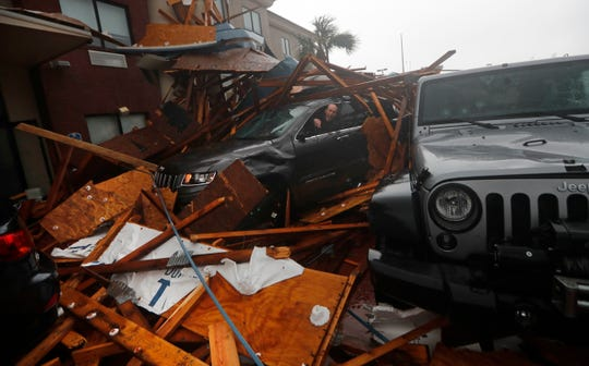 A storm chaser climbs into his vehicle during the eye of Hurricane Michael to retrieve equipment after a hotel canopy collapsed in Panama City Beach on Wednesday, Oct. 10, 2018.