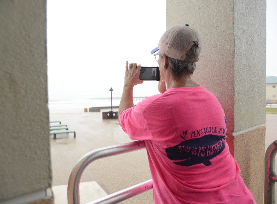 A spectator takes photos of high surf at Casino Beach in Pensacola Beach as Hurricane Michael approaches on Wednesday, Oct. 10, 2018.