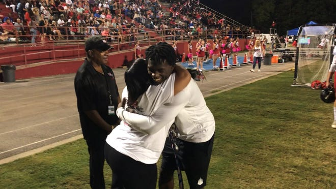 IMG Academy receiver Michael Redding hugs West Florida Principal Shenna Payne while visiting his old team in a game at Pine Forest last Friday.