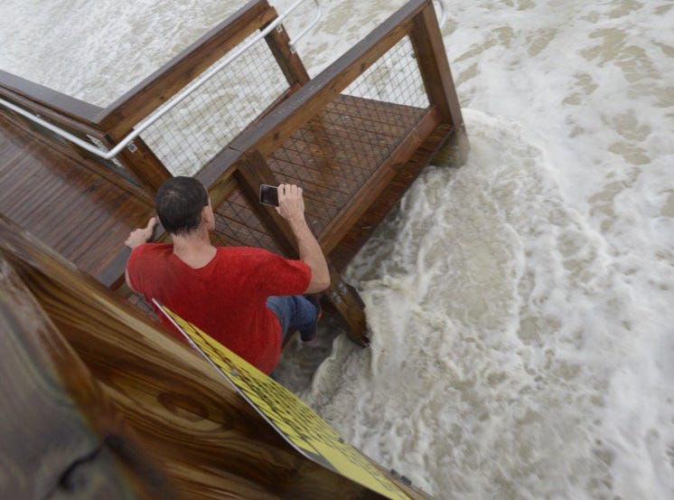Robert Moodyham jumps on railing as wave gets near in Pensacola Beach as Hurricane Michael approaches on Wednesday, Oct. 10, 2018.