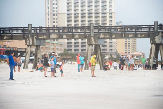 A small crowd gathers to watch the surfers taking advantage of big waves at Casino Beach in Pensacola as Hurricane Michael passes through on Wednesday, October 10, 2018.