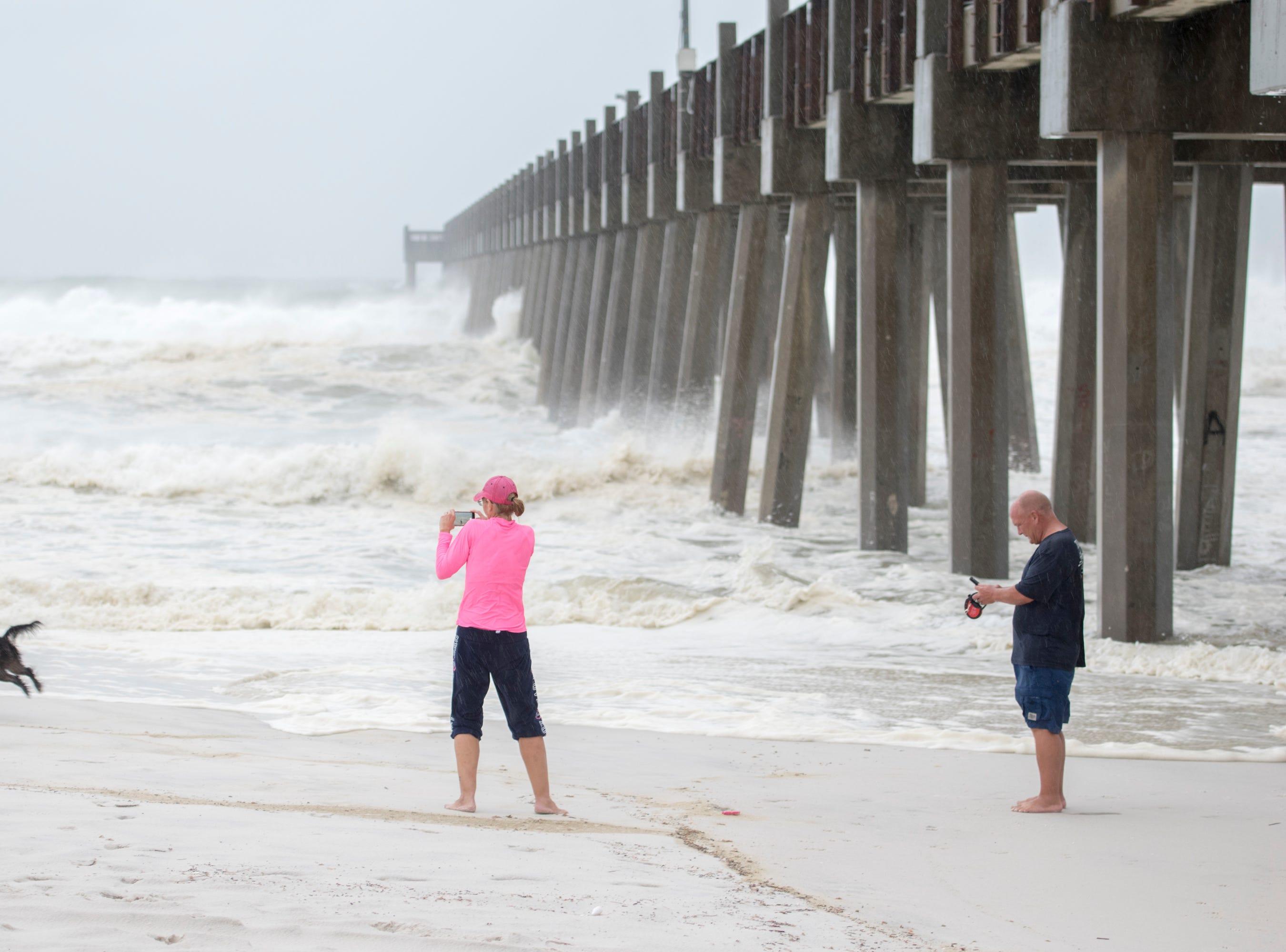 Lisa and Gene Murphy walk their dog Sammy along Casino Beach as Hurricane Michael arrives in Pensacola on Wednesday, October 10, 2018.