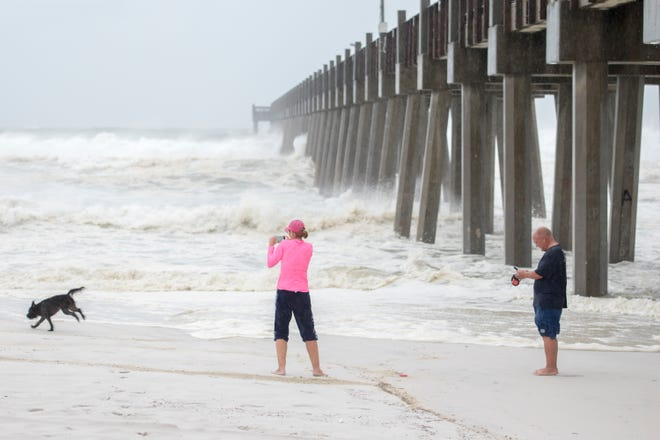 Lisa and Gene Murphy walk their dog Sammy along Casino Beach as Hurricane Michael arrives in Pensacola on Wednesday, October 10, 2018.