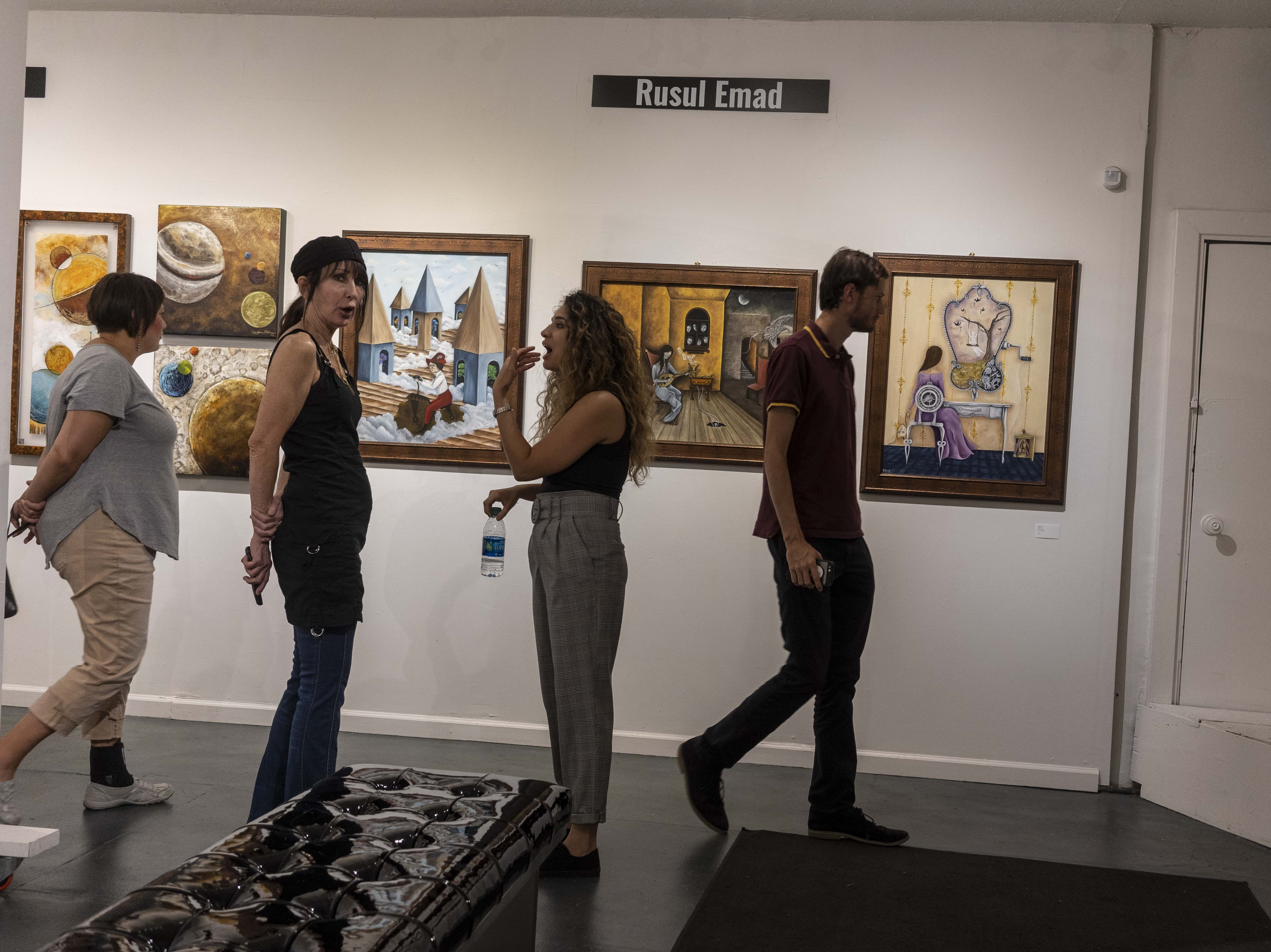 People observe exhibits at 9th Art gallery on Grand Ave during the First Friday Art walk in Downtown Phoenix, on Oct. 5, 2018.
