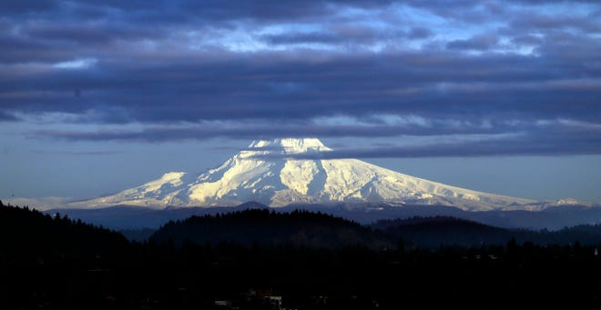 In this Nov. 29, 2016, file photo, Oregon's Mount Hood, sporting a fresh coat of new snow, is lit through dispersing clouds by the setting sun as seen from Portland, Ore. Monitors say Oregon snowpack levels are promising for the early part of the season.