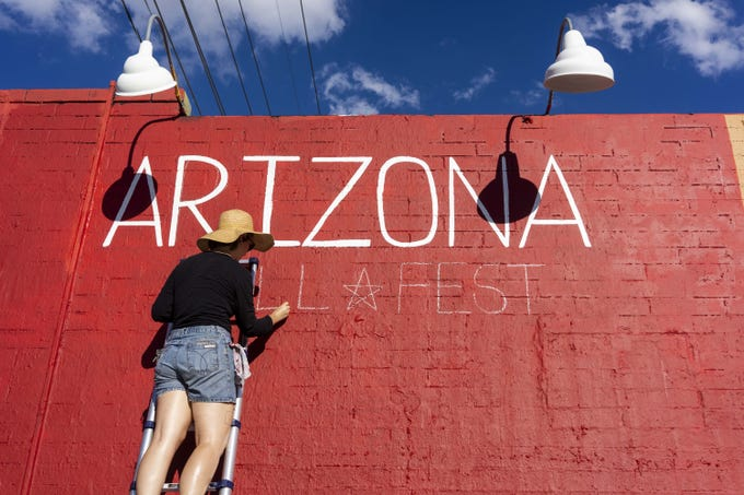 Chelsi Rossi paints Arizona sign get ready for First Friday Art walk in Downtown Phoenix.