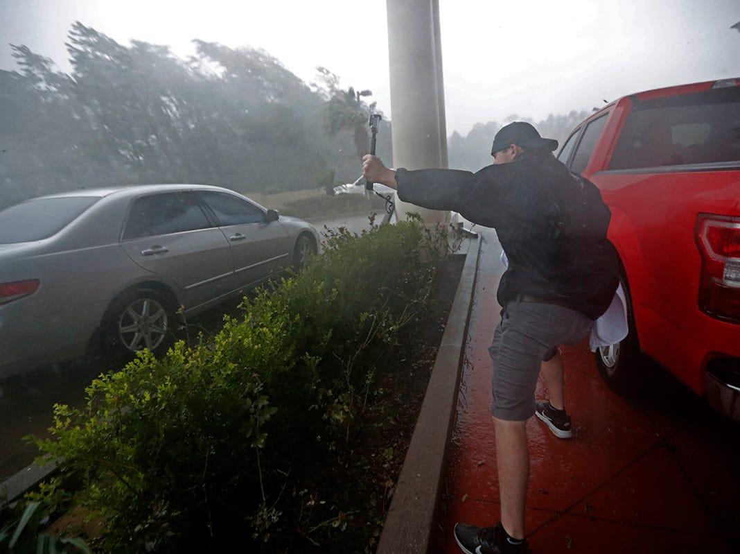 Un cazador de tormentas filma debajo del dosel de un hotel durante el huracán Michael en Panama City Beach, Florida, el miércoles 10 de octubre de 2018.