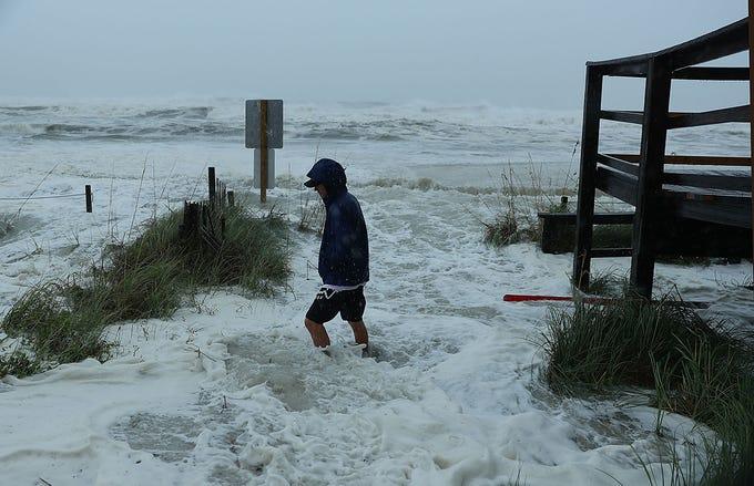 Cameron Sadowski camina a lo largo de donde las olas se estrellan contra la playa cuando las primeras señales del huracán Michael llegan el 10 de octubre de 2018 a Panama City Beach, Florida. Se pronostica que el huracán azotará el Panhandle de Florida en una posible tormenta de categoría 4.
