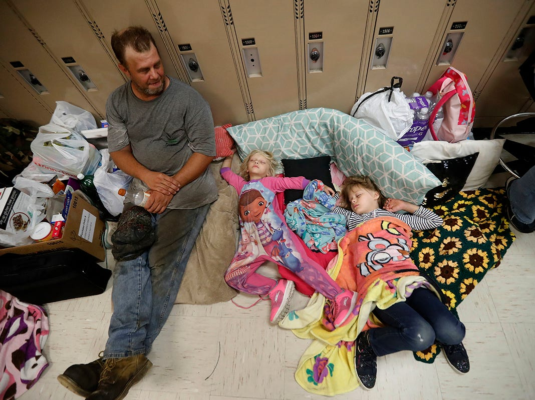 Earnest Sweet se sienta mientras sus hijas Terri, de 4 años, centro, y Anna, de 7, duermen en un refugio de evacuación establecido en Rutherford High School, antes del huracán Michael, que se espera que toque tierra hoy, en Panama City Beach, Florida. , miércoles 10 de octubre de 2018.