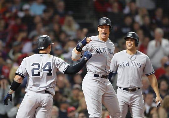 Gary Sanchez # 24 y Aaron Judge # 99 de los Yankees de Nueva York celebran después de que Sánchez conectó un jonrón de tres carreras mientras su compañero Giancarlo Stanton # 27 observa durante la séptima entrada del Juego Dos de la División de la Liga Americana Serie contra los Medias Rojas de Boston en Fenway Park el 6 de octubre de 2018 en Boston, Massachusetts.