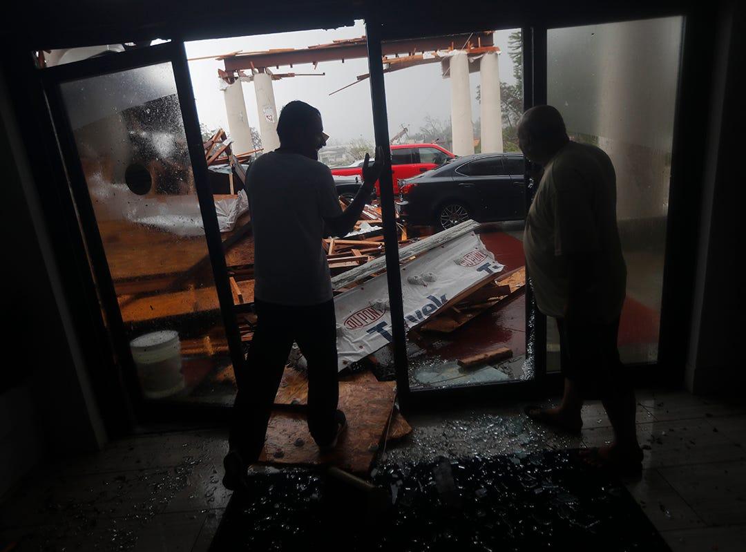Los empleados del hotel observan un toldo que acaba de colapsar, mientras el huracán Michael atraviesa Panamá City Beach, Florida, el miércoles 10 de octubre de 2018.