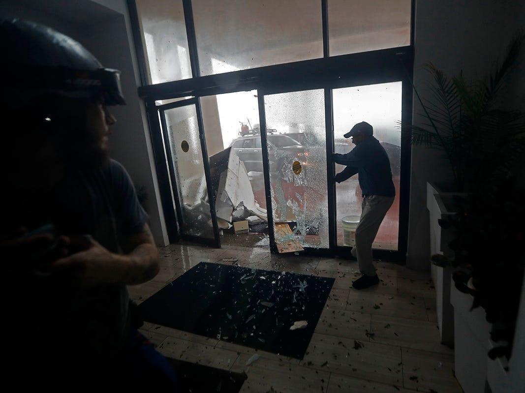 Un empleado del hotel mantiene cerrada una puerta de vidrio cuando se rompe por los escombros que vuelan durante el huracán Michael en Panama City Beach, Florida, el miércoles 10 de octubre de 2018.