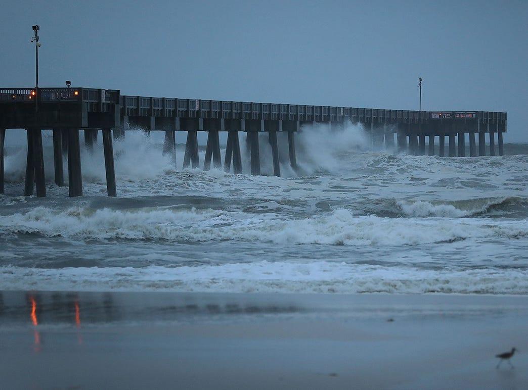 Las olas rompen a lo largo de un muelle cuando las bandas externas del huracán Michael llegan el 10 de octubre de 2018 a Panama City Beach, Florida. Se pronostica que el huracán azotará el Panhandle de Florida en una posible tormenta de categoría 4