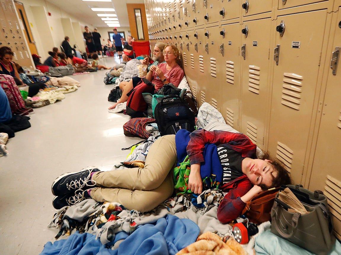Emily Hindle se encuentra en el piso en un refugio de evacuación establecido en Rutherford High School, antes del huracán Michael, que se espera que toque tierra hoy, en Panama City Beach, Florida, el miércoles 10 de octubre de 2018.