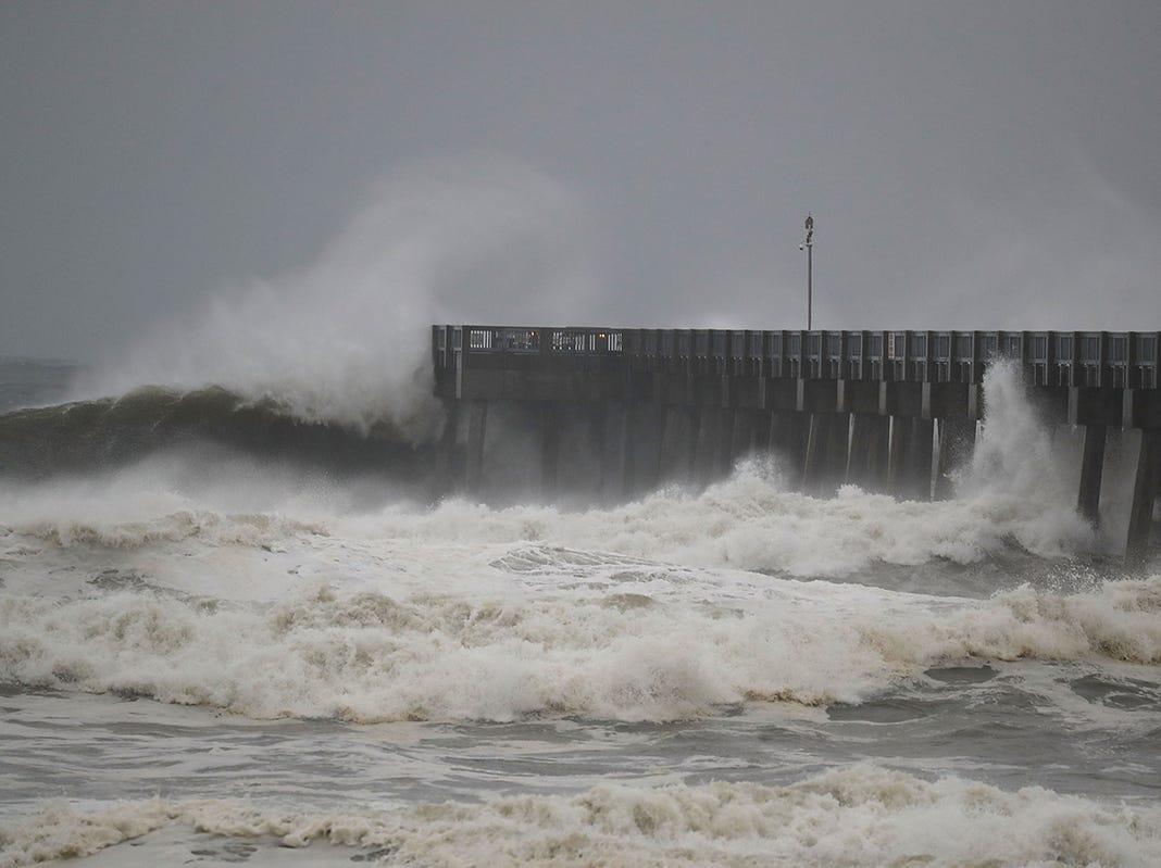 Las olas rompen a lo largo de un muelle cuando las primeras señales del huracán Michael llegan el 10 de octubre de 2018 a Panama City Beach, Florida. Se pronostica que el huracán azotará el Panhandle de Florida en una posible tormenta de categoría 4.