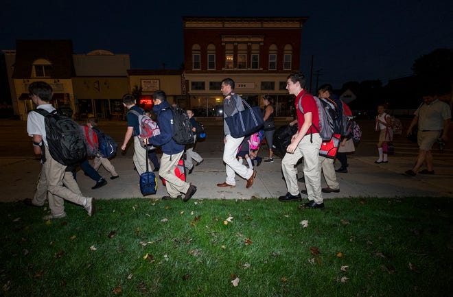 Holy Cross Elementary School students and their parents walk from Marine City Beach to the school on Walk to School Day Wednesday, Oct. 8, 2018 in Marine City.