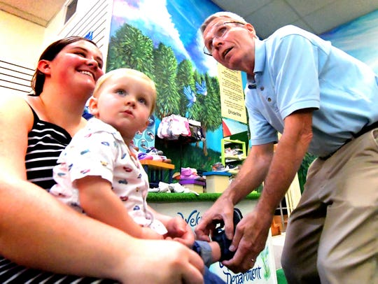 Oliver Poteet, 1, sits with his mother Heather, of Brogue, as he is fitted for shoes by Reineberg's Shoes & Shoe Repair owner Bob Reineberg during the first day of the store's closing sale Wednesday, Oct. 10, 2018. The Springettsbury Township store is closing after 141 years in business. Bill Kalina photo