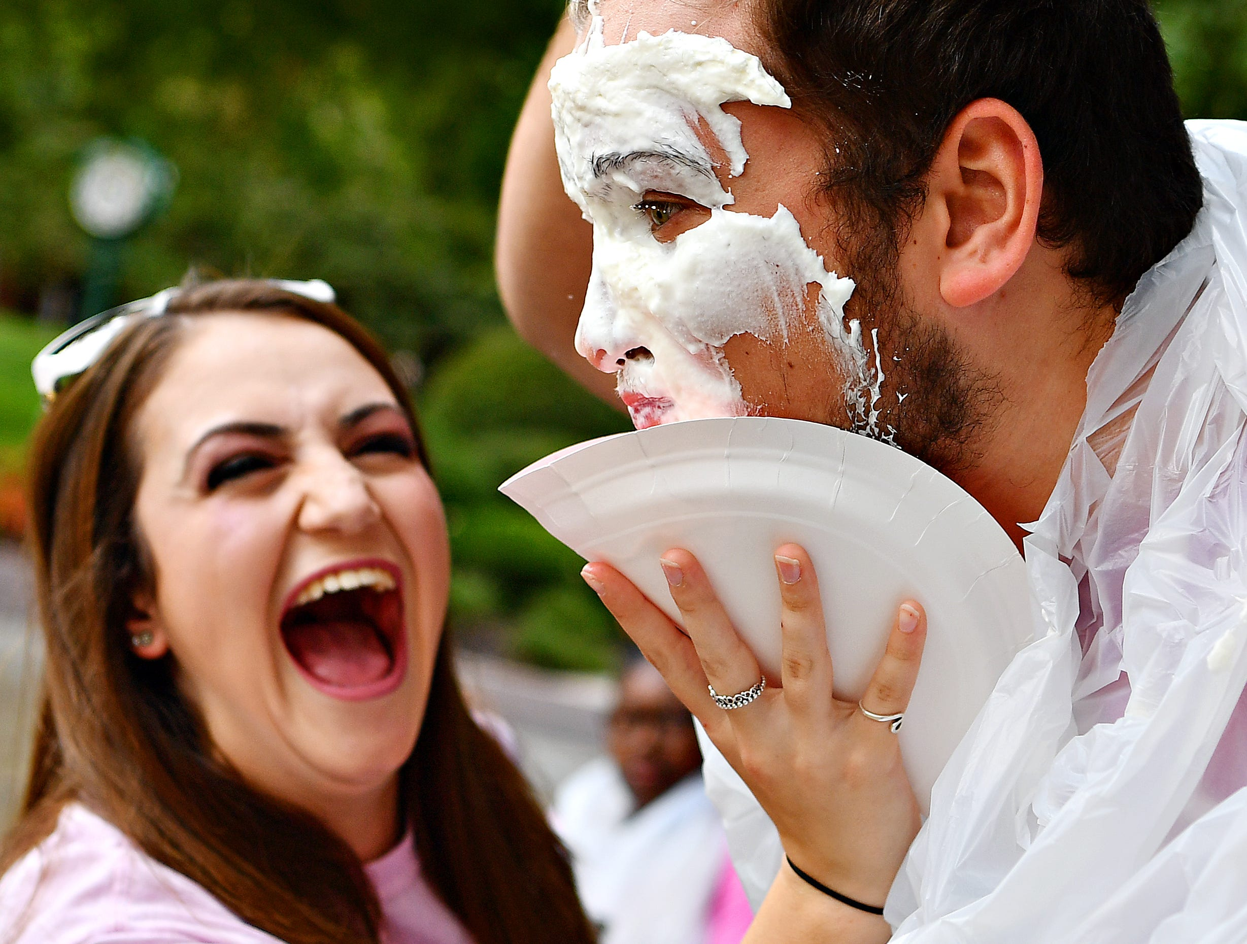 Victoria Cox, left, laughs at student senate member Adam Zeigler's reaction after smashing a plate of whipped cream into his face as York College teams up with the Feel Your Boobies Foundation to raise money in support of breast cancer research during Breast Cancer Awareness Month at York College of Pennsylvania in Spring Garden Township, Wednesday, Oct. 10, 2018. Dawn J. Sagert photo