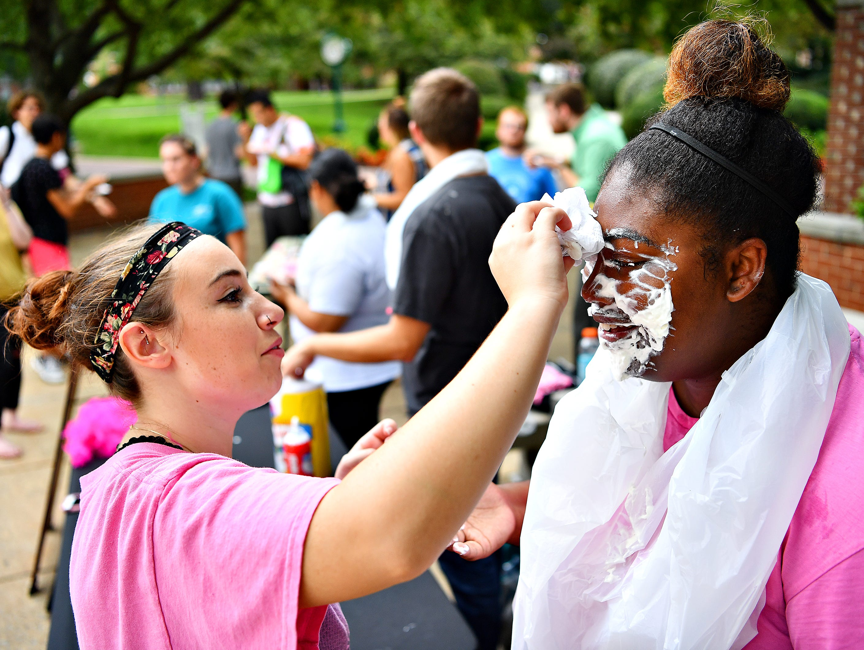 Lexi Biscotto, left, helps Student Senate Member Alexandria Willis after smashing a plate of whipped creme into her face while contributing to the Pie a Senator fundraising event as York College teams up with Feel Your Boobies Foundation to raise money in support of breast cancer research during Breast Cancer Awareness Month at York College of Pennsylvania in Spring Garden Township, Wednesday, Oct. 10, 2018. Dawn J. Sagert photo