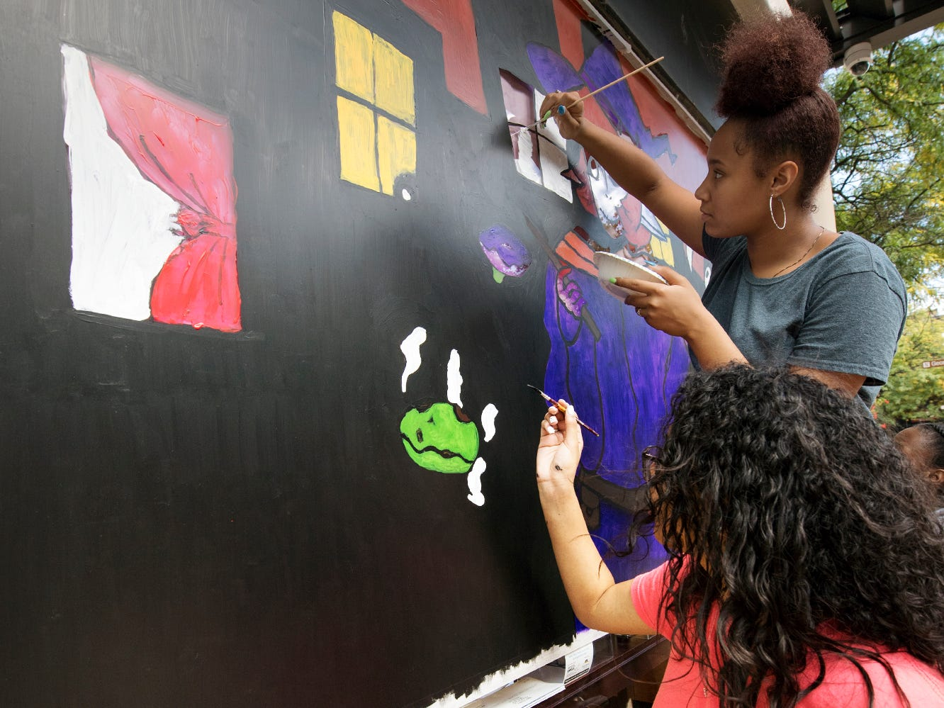 William Penn students Stayce Figveroa, bottom, and Michayla Roberts paint a Halloween window display in downtown York Wednesday October 10, 2018.