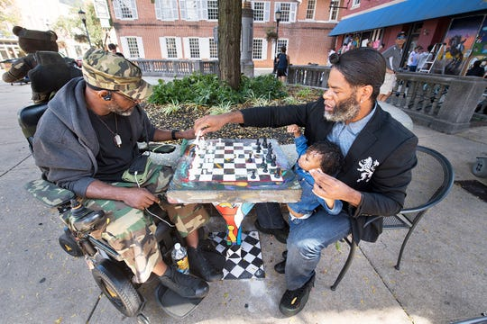 """Kevin """"Po"""" Bertram, right, plays a game of chess with friend Smitty on Continental Square in York Wednesday on one of the permanently installed chess tables."""