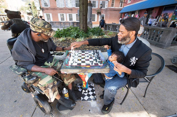 "Kevin ""Po"" Bertram, right, plays a game of chess with friend Smitty on Continental Square in York Wednesday October 10, 2018 on one of the permanently installed chess boards. ""Chess brings together all walks of life...it brings together strong thinkers,"" Bertram said."