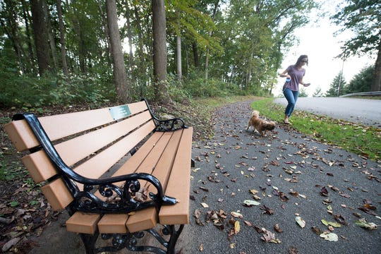 A woman walks her dog on an existing walking trail between Normandie Ridge and the woods that will become the senior walking trail in West Manchester Township.