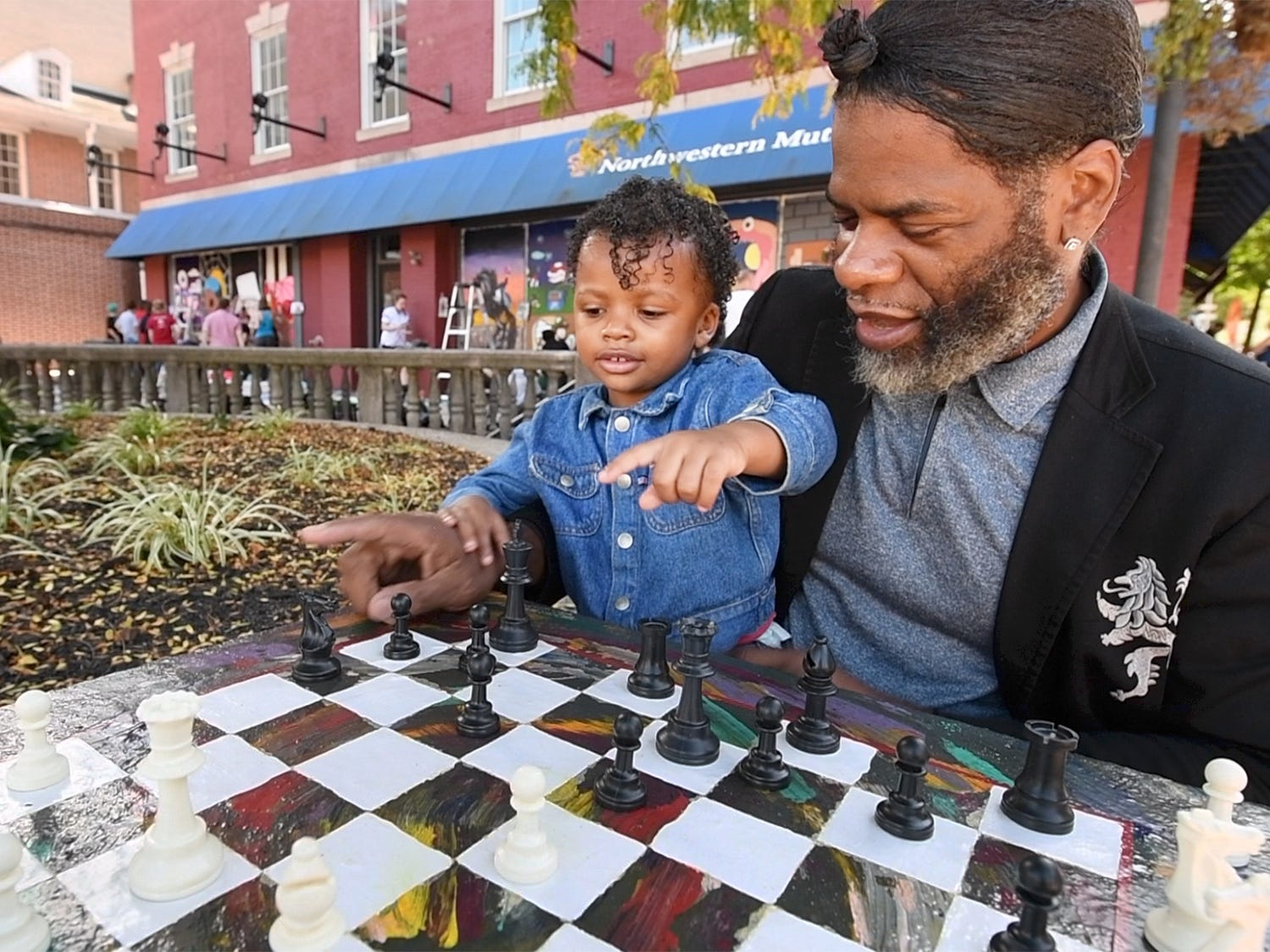 "Kevin ""Po"" Bertram, right, asks his 3-year-old daughter, Queen Amyriah, what the names of the chess pieces are on one of three permanent chess boards recently installed on Continental Square in York. He sees the game, and the tables, as a common ground for different people to make friends. He adds that while the game is competitive, it's civil, with competitors always shaking hands before a competition."