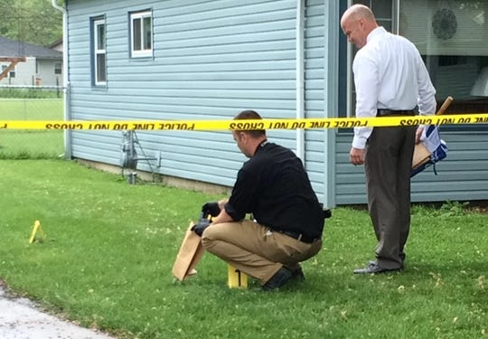 Rick Thalls (left) and Randy Retter collect evidence at the scene of a 2015 shooting in Centerville.