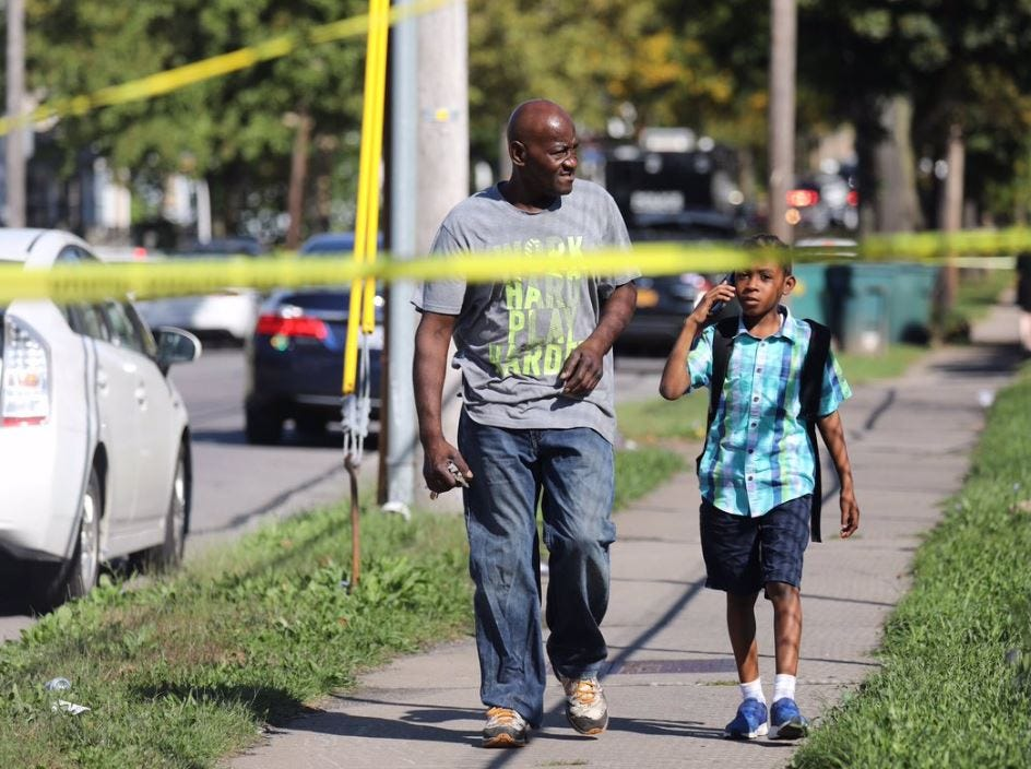 Crime scene tape surrounds a man and a child walking in the Goodman and Bay streets area after multiple shootings Wednesday morning.
