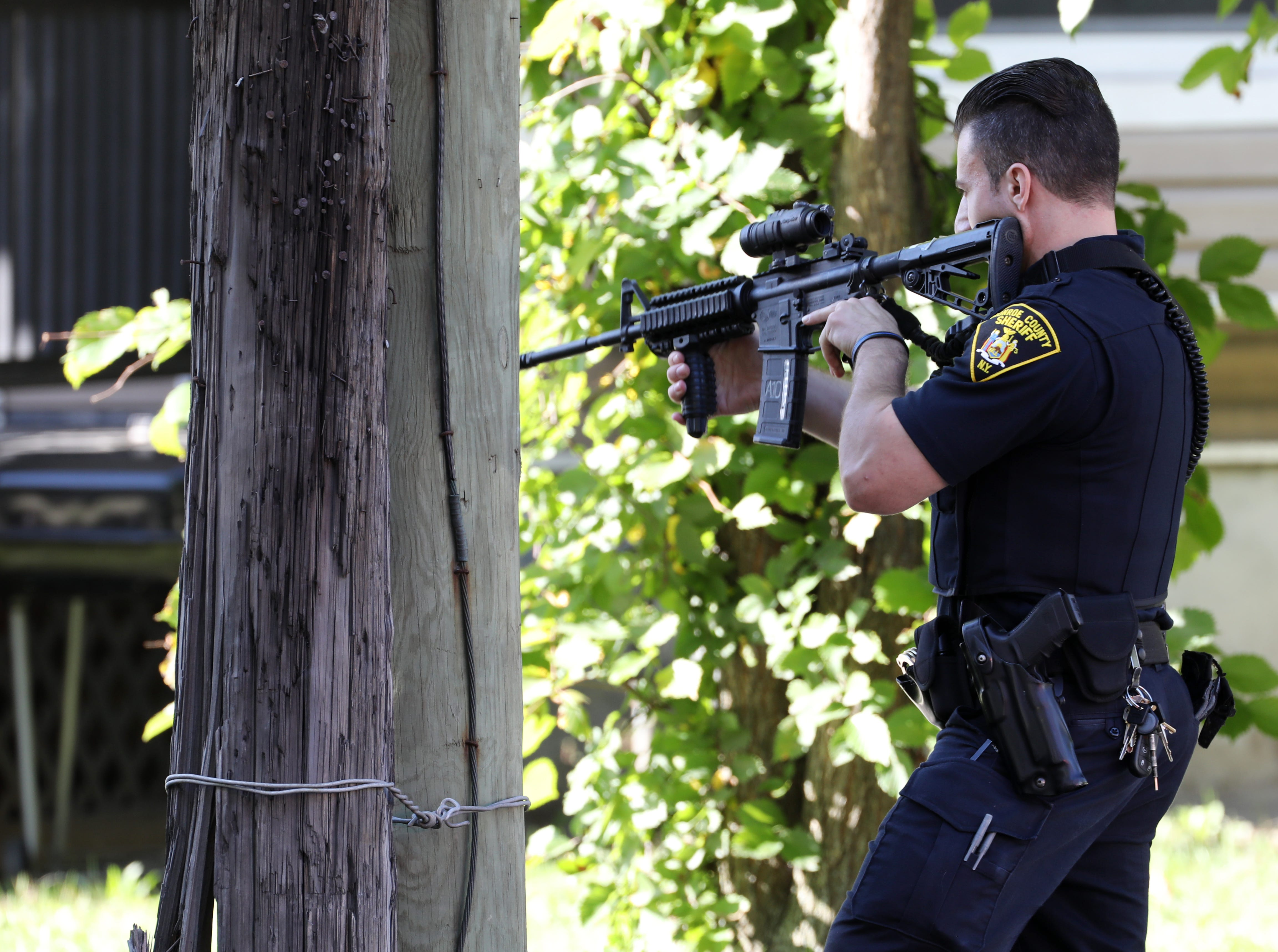 A Monroe County sheriff deputy points  his weapon south toward Bay Street on the corner of  Forester Street and North Goodman Street near School 25 as police chase a homicide suspect  in a van east on Bay Street in Rochester.